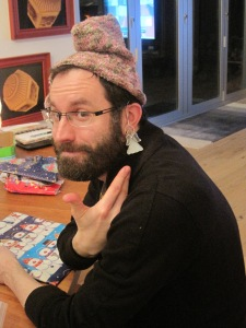 "N sporting a sweet faux earring. It's an ornament that my m.i.l. found from decades ago. And the sack knit ""hat"" was done by my s.i.l."